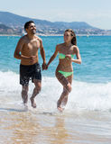 Smiling couple running. Smiling young couple running on the beach royalty free stock photo
