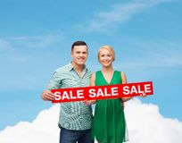 Smiling couple with sale sign Stock Photo