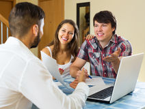 Smiling couple and salesman talking. Cheerfully about purchase at home royalty free stock image