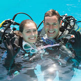 Smiling couple on scuba training in swimming pool showing ok gesture Royalty Free Stock Photos