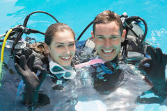 Smiling couple on scuba training in swimming pool showing ok gesture Stock Photo