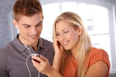 Smiling couple sharing earphones. Smiling young couple listening to music together, sharing earphones Stock Photo