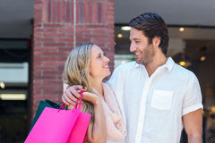 Smiling couple with shopping bags embracing Royalty Free Stock Images