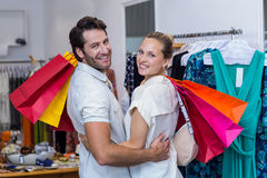 Smiling couple with shopping bags embracing Stock Photos