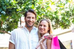 Smiling couple with shopping bags embracing Stock Image