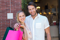 Smiling couple with shopping bags embracing Royalty Free Stock Photography