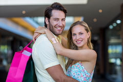 Smiling couple with shopping bags embracing Stock Photo