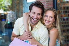 Smiling couple with shopping bags embracing Royalty Free Stock Photos