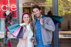 Smiling couple with shopping bags in front of window Royalty Free Stock Image
