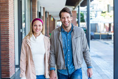 Smiling couple with shopping bags holding hands Stock Images