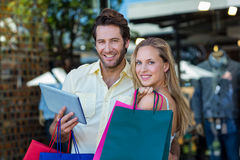 Smiling couple with shopping bags holding tablet computer. Portrait of smiling couple with shopping bags holding tablet computer at shopping mall Royalty Free Stock Photography