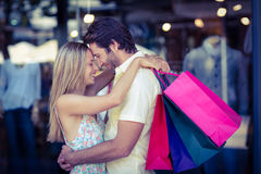 Smiling couple with shopping bags hugging closely Stock Images