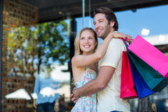 Smiling couple with shopping bags hugging Stock Photos