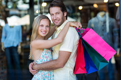 Smiling couple with shopping bags hugging Royalty Free Stock Photos