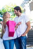 Smiling couple with shopping bags laughing Royalty Free Stock Image