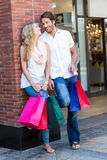 Smiling couple with shopping bags leaning on the wall Royalty Free Stock Images