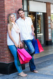 Smiling couple with shopping bags leaning on the wall Stock Photo