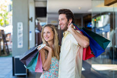 Smiling couple with shopping bags looking far away Stock Photo