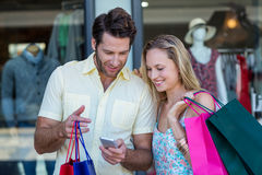 Smiling couple with shopping bags looking at smartphone Stock Photo