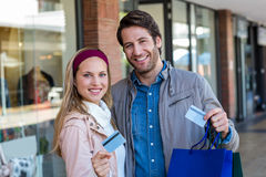 Smiling couple with shopping bags showing credit card Royalty Free Stock Photography