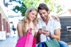 Smiling couple with shopping bags sitting and using smartphone. At shopping mall Stock Images