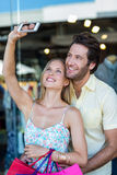 Smiling couple with shopping bags taking selfies Stock Images