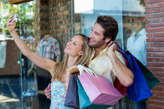 Smiling couple with shopping bags taking selfies Royalty Free Stock Image