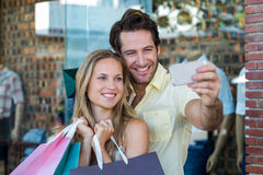 Smiling couple with shopping bags taking selfies Stock Image