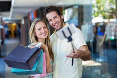 Smiling couple with shopping bags taking selfies with selfiestick Royalty Free Stock Photo
