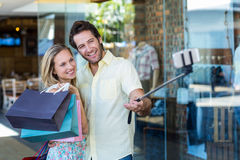 Smiling couple with shopping bags taking selfies with selfiestick Royalty Free Stock Image