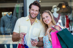 Smiling couple with shopping bags using smartphone Stock Images