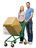 Smiling couple with shopping cart and big box Stock Photos