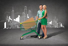 Smiling couple with shopping cart and big box. Happiness,electronics, shopping and couple concept - smiling couple with shopping cart and big cardboard box in it Royalty Free Stock Photo