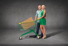 Smiling couple with shopping cart and big box Royalty Free Stock Photos
