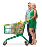 Smiling couple with shopping cart and food in it Royalty Free Stock Images