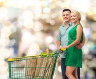 Smiling couple with shopping cart and food in it Stock Image