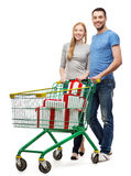 Smiling couple with shopping cart and gift boxes. Happiness, holidays, shopping and couple concept - smiling couple with shopping cart and gift boxes in it Royalty Free Stock Images