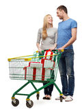 Smiling couple with shopping cart and gift boxes Royalty Free Stock Images