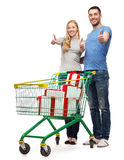 Smiling couple with shopping cart and gift boxes Royalty Free Stock Photos