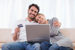 Smiling couple shopping online Stock Image