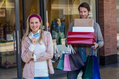 Smiling couple showing credit card and carrying boxes Stock Images