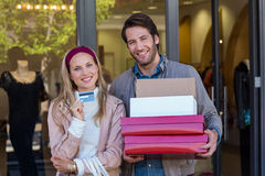 Smiling couple showing credit card and carrying boxes Royalty Free Stock Photos