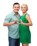 Smiling couple showing heart with hands Stock Images