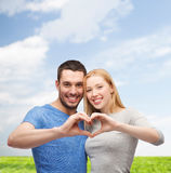 Smiling couple showing heart with hands Royalty Free Stock Images