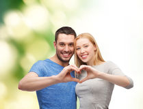 Smiling couple showing heart with hands Royalty Free Stock Image