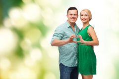 Smiling couple showing heart with hands. Love and family concept - smiling couple showing heart with hands royalty free stock photo