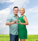 Smiling couple showing heart with hands Stock Image