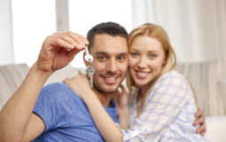 Smiling couple showing keys over room background Stock Photo