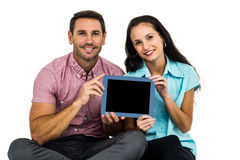 Smiling couple showing tablet at the camera Royalty Free Stock Photos