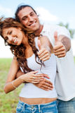 Smiling couple showing thumbs-up Stock Photos